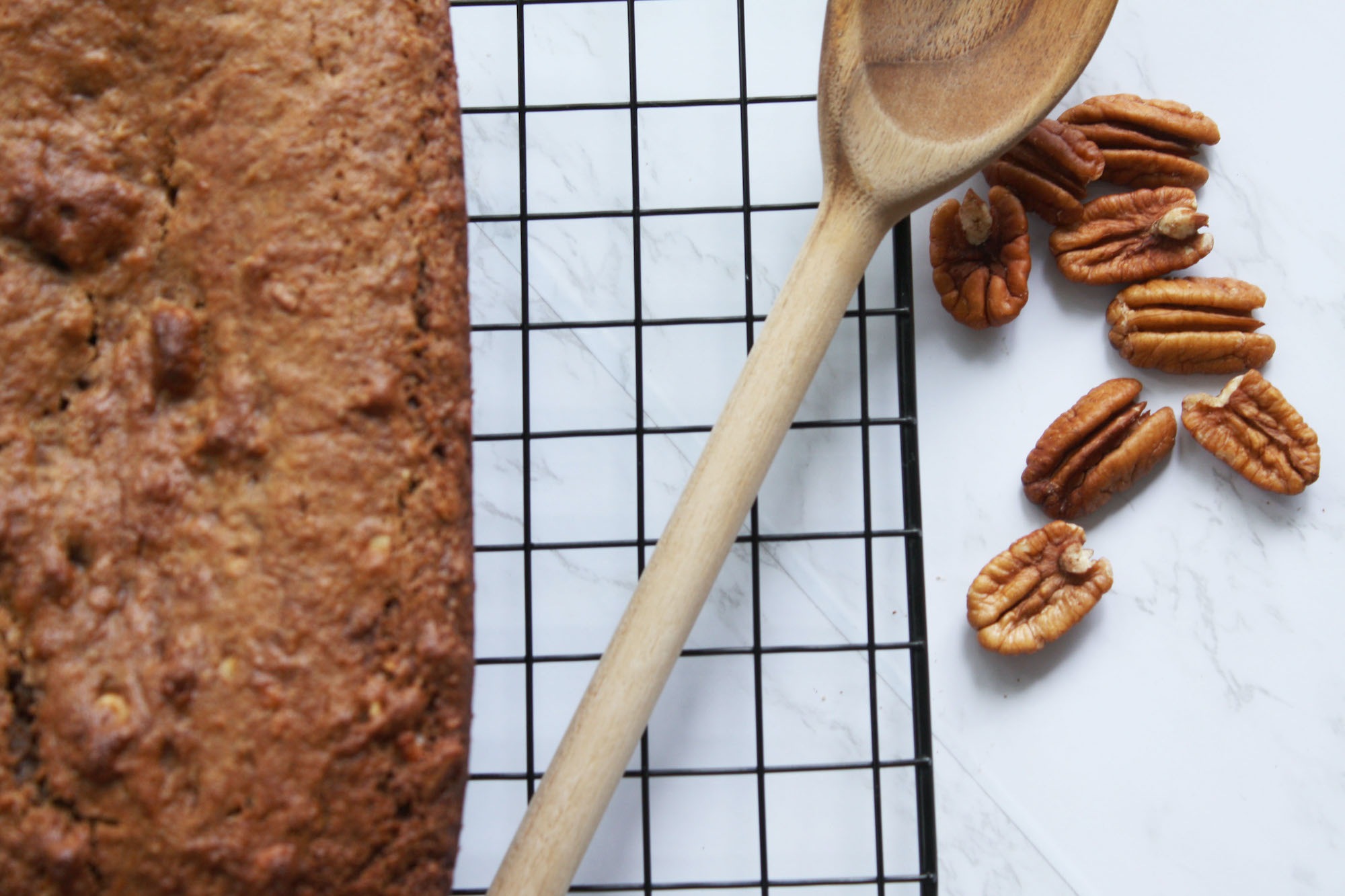 cinnamon pecan banana bread loaf overhead shot with wooden spoon and a handful of pecans   hearth health happiness