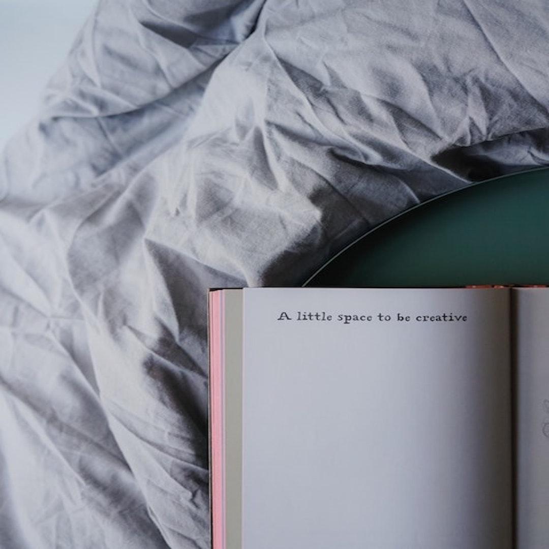 journal on comforter | image by toa heftiba on unsplash