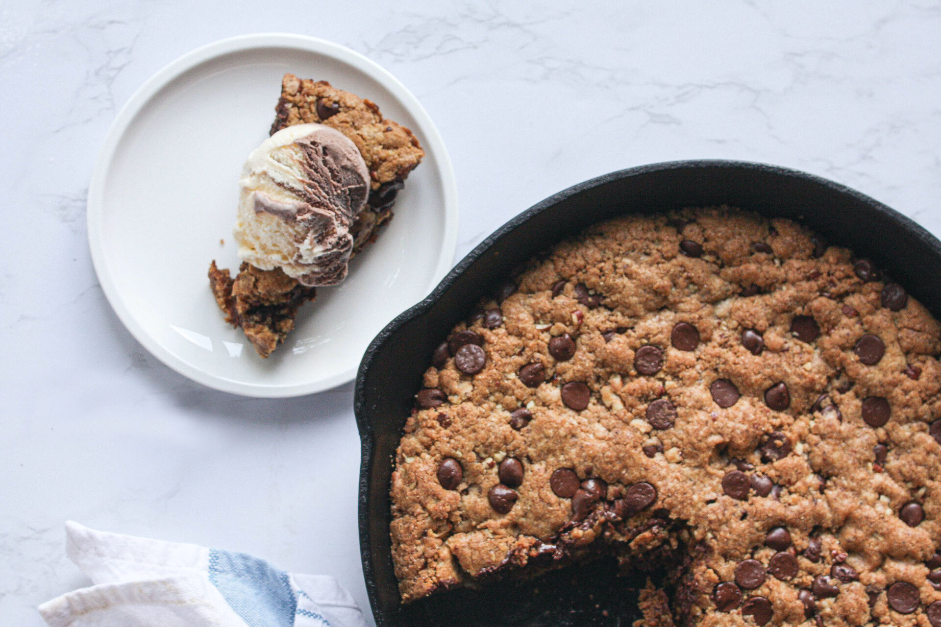 cookie in a large cast iron skillet with a slice removed and topped with ice cream | hearth health happiness