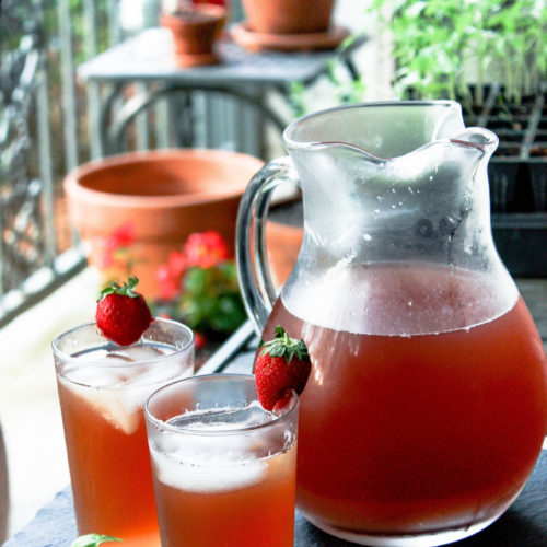 pitcher of strawberry basil iced tea with two additional glasses on outdoor table   food blog   summertime drinks   hearth health happiness