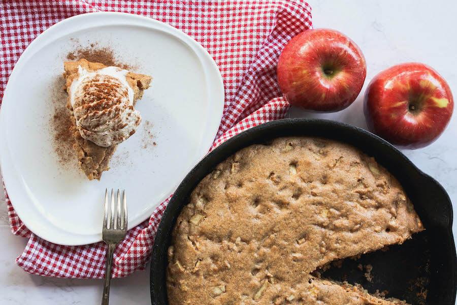 overhead image of apple cinnamon skillet cake with slice next to skillet
