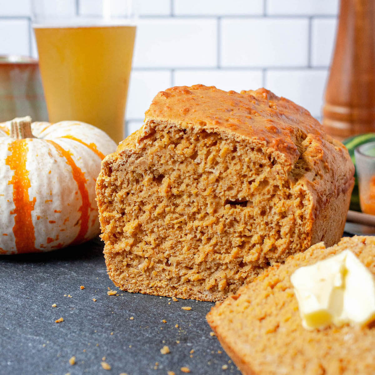 pumpkin beer bread on counter with slice in foreground