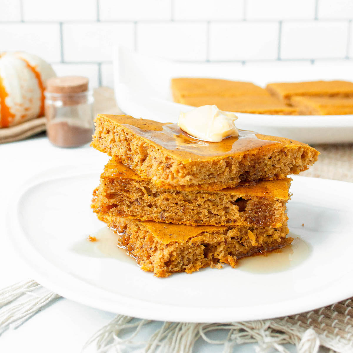 pumpkin spice sheet pan pancakes stacked with syrup
