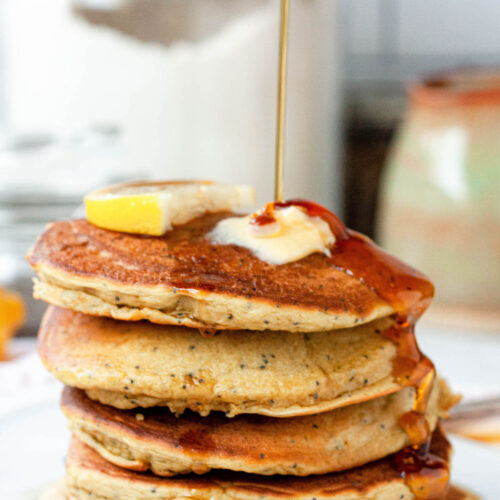 stack of vegan lemon poppy seed pancakes with maple syrup pour