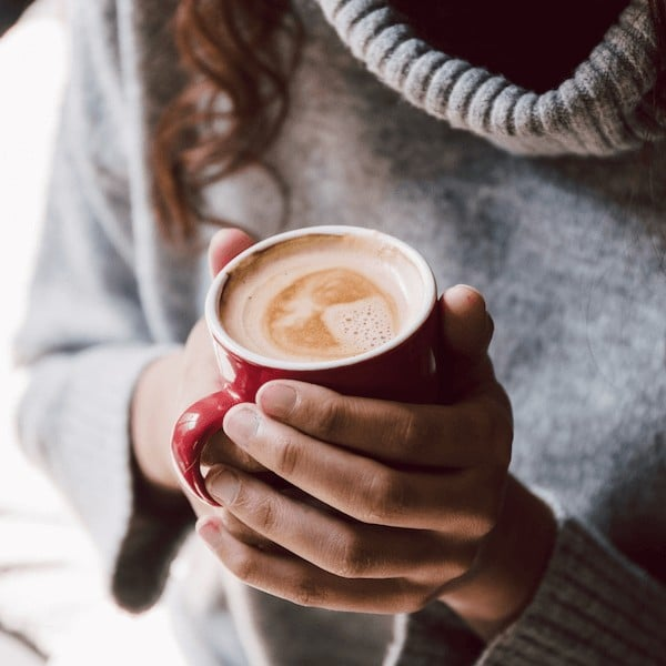 Woman in sweater holding full coffee mug